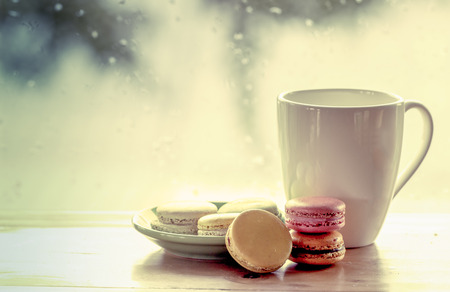 rain: Colorful macaroons and coffee cup on  rainy day window background in sweet color tone
