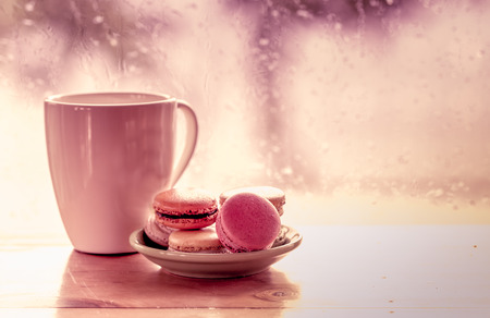 Colorful macaroons and coffee cup on  rainy day window background in sweet color tone