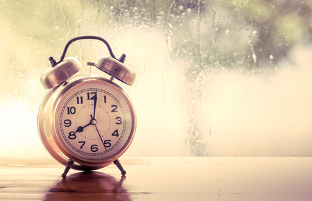 retro alarm clock on wooden table on  rainy day window background  in vintage color tone