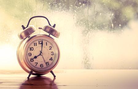 orologi antichi: sveglia retr� su tavola di legno su finestra piovosa giornata di sfondo in tonalit� di colore d'epoca