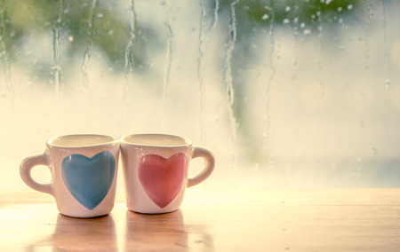 love: two lovely glass on rainy day window background  in vintage color tone