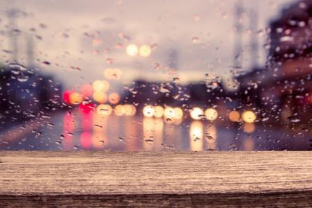 gotas de agua: mesa de madera con vista al tráfico de la falta de definición a través de un parabrisas del coche cubierto de la lluvia para el fondo