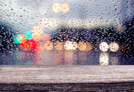 autumn rain: wooden table with blur traffic view through a car windscreen covered in rain for background