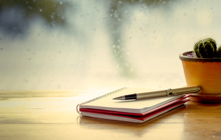 Pen on notebook on  rainy day window background  in vintage color tone Reklamní fotografie