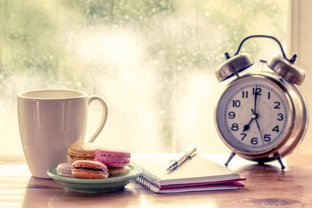 ventanas abiertas: Macarrones coloridos y taza de café con la pluma en el cuaderno y despertador en fondo de la ventana lluviosa día en el tono del color de la vendimia