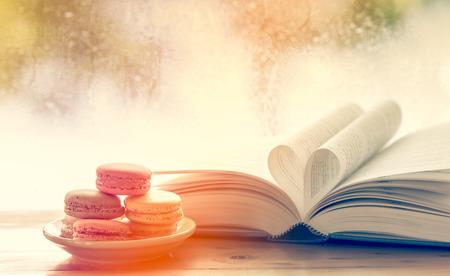 kleurrijke bitterkoekjes en hart boekpagina op regenachtige dag venster op de achtergrond in zoete kleurtoon