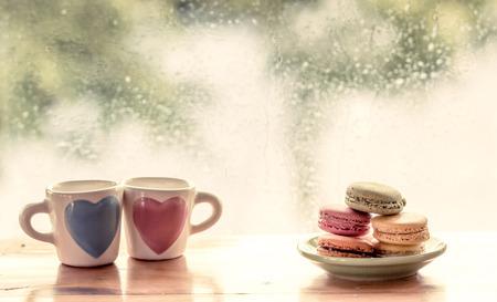 bitterkoekjes met mooie glas op regenachtige dag venster achtergrond in zoete kleurtoon