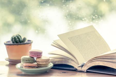 Kleurrijke makaron en pen op open boek op de regenachtige achtergrond van het dagvenster in uitstekende kleurentoon