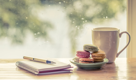 Pen on notebook with books decorate with macaroon on  rainy day window background  in vintage color tone