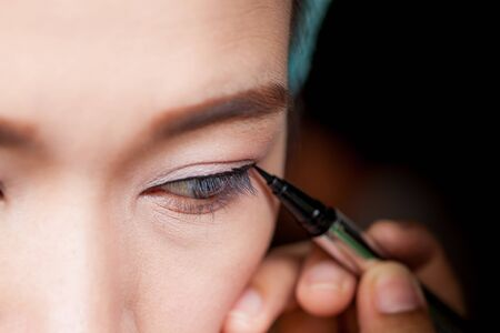 eyeliner: Makeup concept, Closeup asian woman applying eyeliner on eye