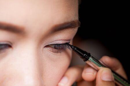 mujer maquillandose: Concepto de maquillaje, Primer mujer asi�tica aplicar delineador en los ojos