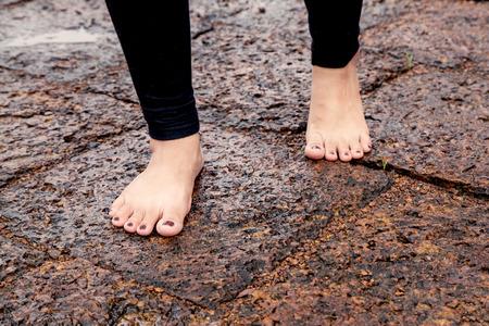 bare feet: Woman bare feet walking on wet rocky pavement after rain
