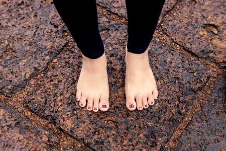 Woman bare feet on wet rocky pavement after rain