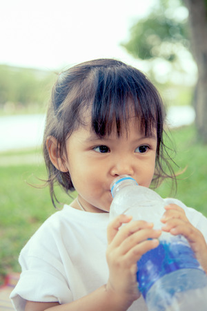 tried: Child is drinking water in the park in vintage color filter Stock Photo