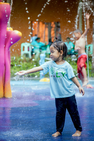 asian toddler: Child little girl having fun to play with water in park fountain in summer time Stock Photo