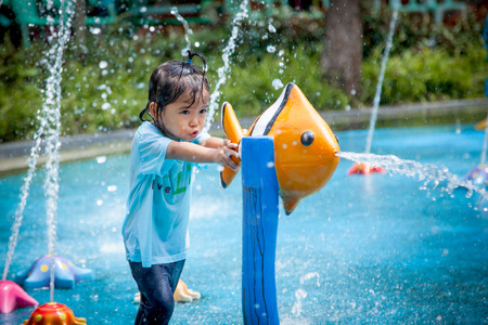 Child little girl having fun to play with water in park fountain in summer time Stock Photo