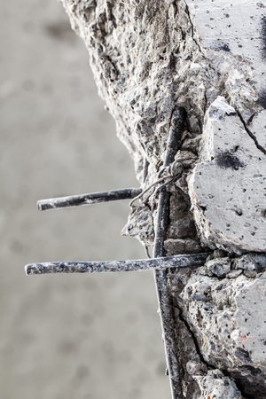 protruding: Steel rods protruding from the cracked concrete