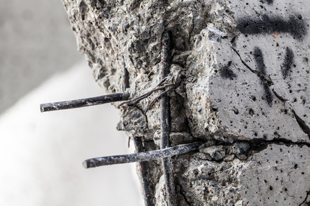 cracked concrete: Steel rods protruding from the cracked concrete
