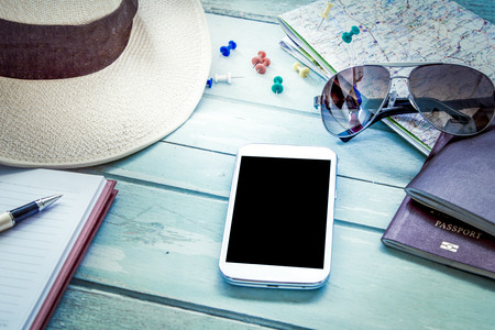 Preparation for travel, cellphone, sunglasses ,passport, road map,hat and notebook on wooden table in blue vintage color filter