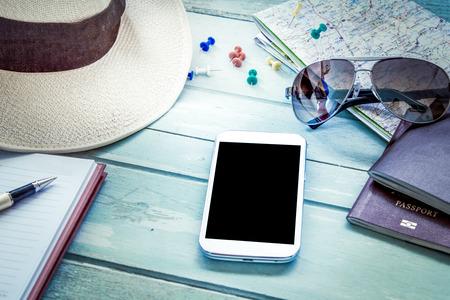 Vorbereitung für die Reise, Handy, Sonnenbrille, Reisepass, Straßenkarte, Hut und Notebook auf Holztisch in blau Vintage Farbfilter Standard-Bild - 44866532