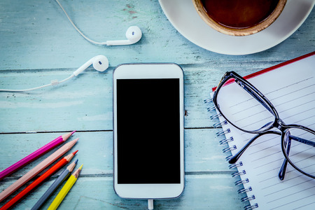 Smartphone,cellphone,notebook,pencil color,glasses and coffee on wooden table in blue vintage filter