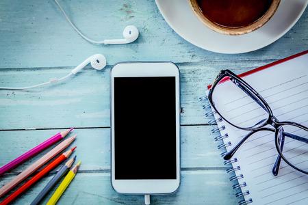 Smartphone, mobiele telefoon, notebook, potlood kleur, glazen en koffie op houten tafel in blauwe vintage filter