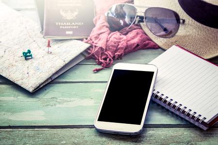 Voorbereiding voor reizen, mobiele telefoon, zonnebril, paspoort, wegenkaart, hoed en notebook op houten tafel in vintage filter