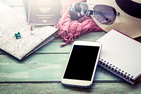 Preparation for travel, cellphone, sunglasses ,passport, road map,hat and notebook on wooden table in vintage filter Standard-Bild
