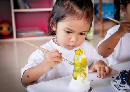 Kinderen schilderen, klein meisje met plezier om op te schilderen stucwerk pop, selectieve aandacht op Stockfoto