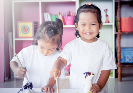 asian art: Child painting, two little girl having fun to paint on stucco doll together on bookshelf background,selective focus Stock Photo