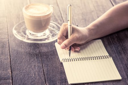 Woman hand writing on notebook over wooden table with coffee cup in vintage color filter