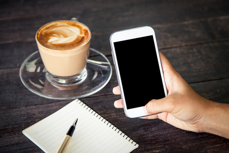 Women hand using smartphone,cellphone,tablet over wooden table with notebook and coffee cup Reklamní fotografie