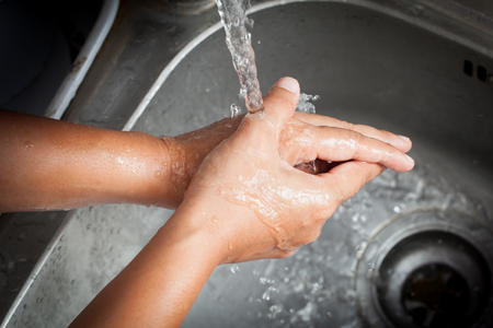 jabon liquido: Mujer que se lava las manos bajo agua corriente en sitio de la cocina Foto de archivo