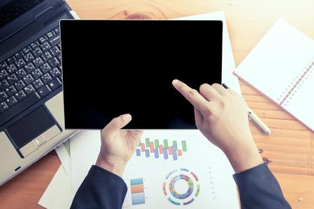 informe: Empresaria mano que sostiene la tablilla y analizar el informe de negocio, trabajando sobre el escritorio de madera en la oficina de filtro de color de la vendimia Foto de archivo