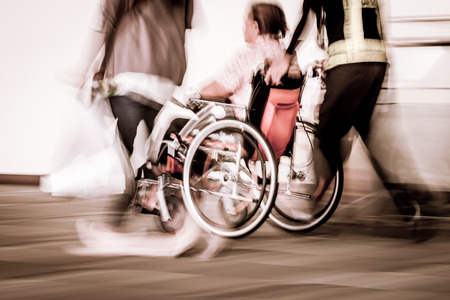 Blur motion of disabled person sit in wheelchair and passengers walking in the airport, vintage filter effect