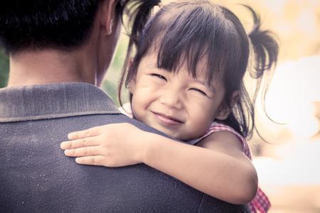hombros: Padre e hijo, la niña feliz descansando sobre el hombro de su padre en el parque, efecto de filtro de la vendimia
