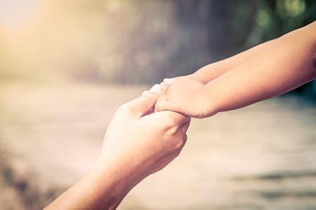mama e hijo: La madre y su mano de juntas con amor en el parque infantil, el filtro de la vendimia