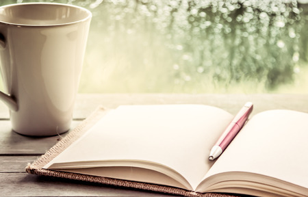 Pen on open notebook and coffee cup in rainy day window background, vintage filter