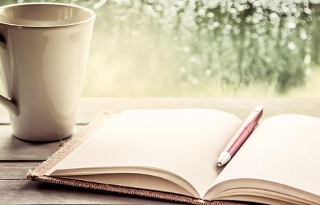 Pen op open notebook en kopje koffie in regenachtige dag venster op de achtergrond, vintage filter