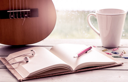 Pen on open notebook on guitar and coffee cup in rainy day window background, vintage filter Stock Photo