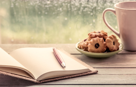 Pen on open notebook with cookies and coffee cup in rainy day window background, vintage filter