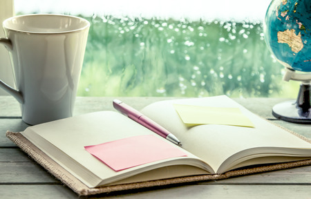 Pen and sticky note on open notebook on coffee cup and globe in rainy day window background, vintage filter