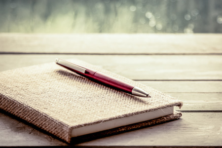 Pen on notebook on wooden table in rainy day window background, vintage filter Reklamní fotografie