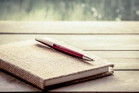 papel de notas: Pluma en el cuaderno en la mesa de madera en la ventana de fondo d�a de lluvia, filtro de la vendimia Foto de archivo