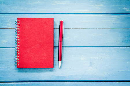 Red notebook with pen on blue wooden table