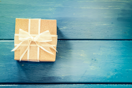 Gift box on blue wooden table,vintage filter Standard-Bild