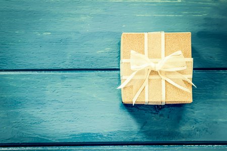 Gift box on blue wooden table,vintage filter Reklamní fotografie