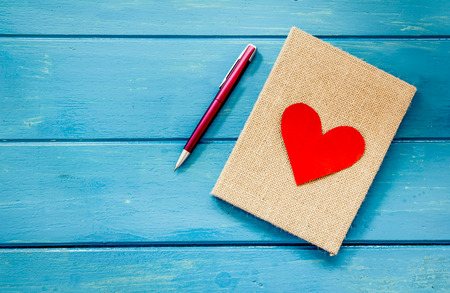 love heart on notebook with pen on blue wooden table