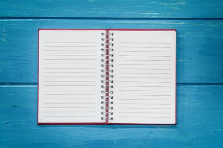 espiral: cuaderno abierto en blanco en la mesa de madera azul Foto de archivo