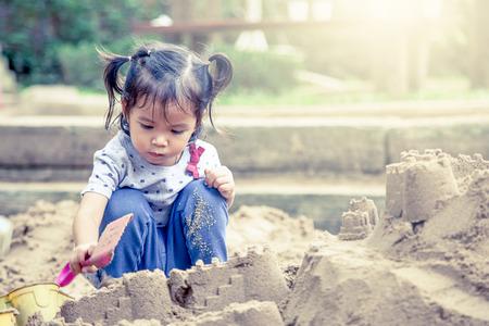 Kind spelen met zand in de speeltuin, vintage filter Stockfoto